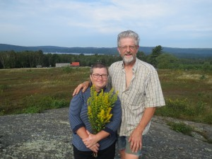 Richard and Maria on top of their new world, surrounded by their wild blueberries.. She picked the flowers on the way up. Visible are their home and barn, and far back, Lake St. George.